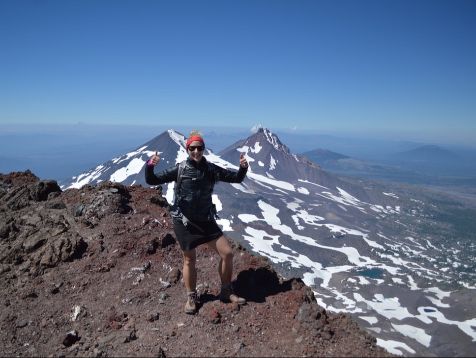 Franziska Weinheimer who is the owner of Hike Oregon, standing on a the summit of South Sister